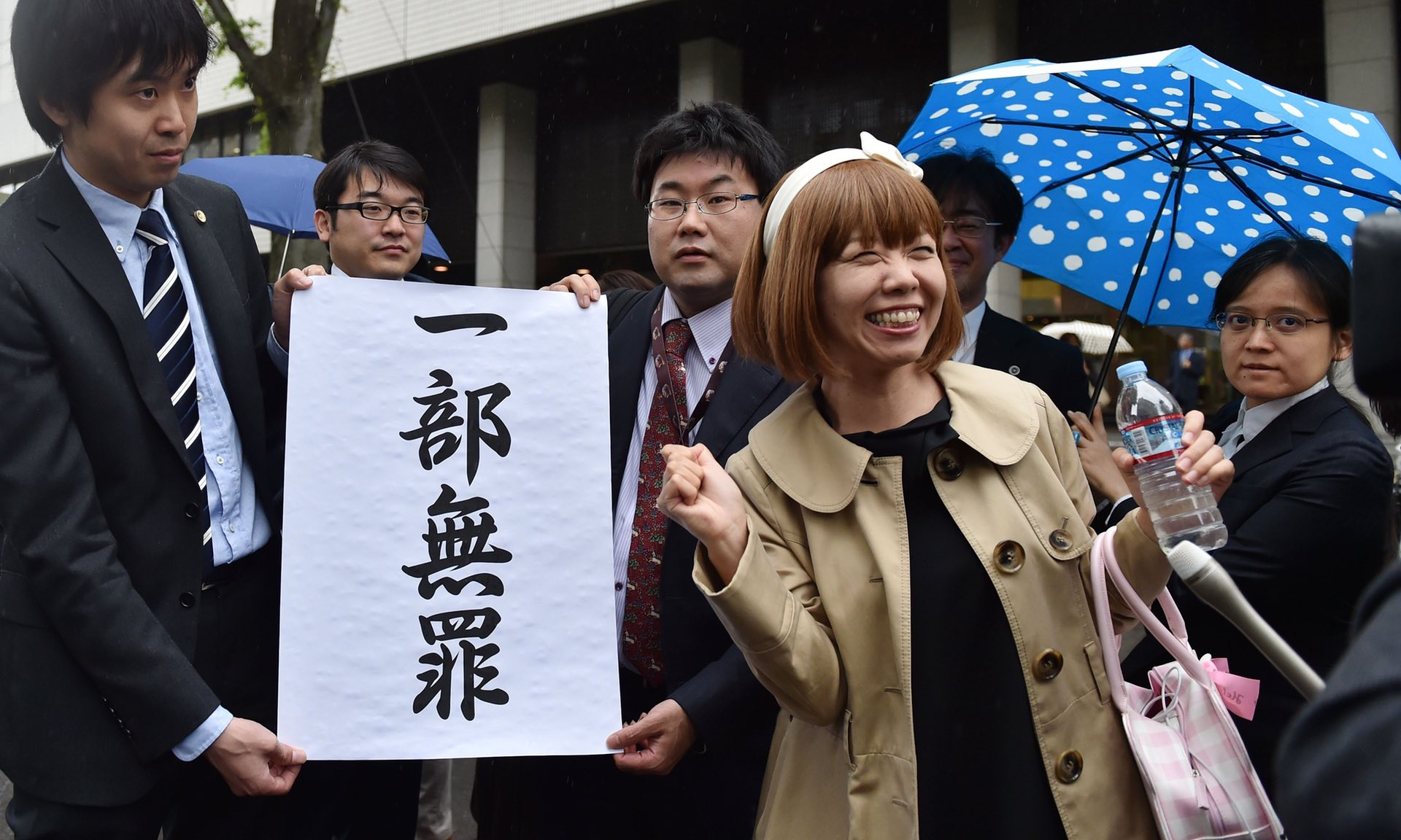 Megumi Igarashi and her lawyers pose with a sign reading 'a part is not guilty' in front of the Tokyo court